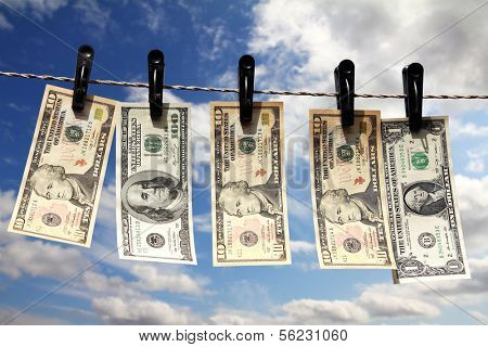 paper dollars are drying on rope under blue sky