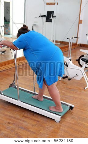 fitness - overweight woman running on trainer treadmill
