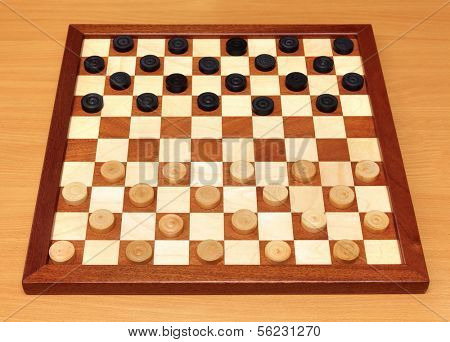 wooden checkerboard with checkers spaced on table