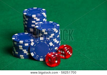 Blue Poker Chips And Red Cubes On The Green Table