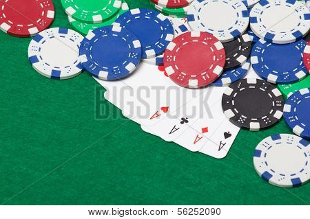 Poker Chips And Four Aces On A Green Table Background