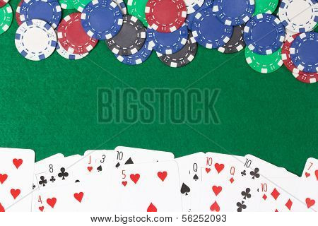 Poker Chips And Cards On A Green Table Background