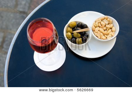 Parisian street cafe table with traditional French aperitif kir cassis and nibbles. Focus on nibbles