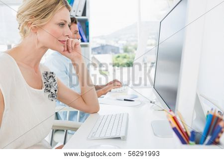 Side view of smiling casual young couple working on computers in a bright office