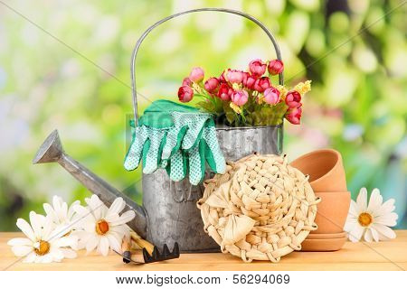 Gardening tools and flowers on wooden table, outdoors