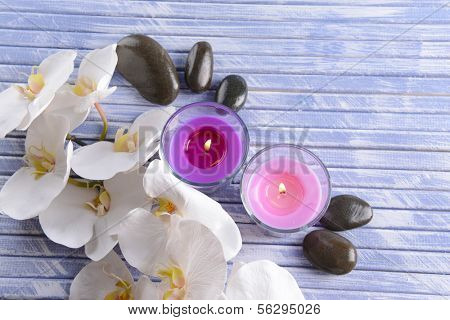Beautiful colorful candles, spa stones and  orchid flower,on color wooden background
