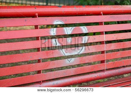 A Silver Heart Painted On A Red Bench