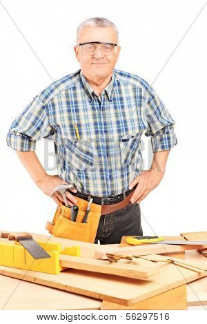 Middle aged male carpenter standing behind working table, isolated on white background