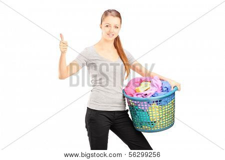 Young woman with laundry basket full of clothes giving thumb up, isolated on white background