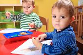 stock photo of day care center  - Cute european toddlers drawing a picture in kindergarten - JPG