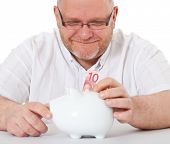 Charismatic middle aged man puts 10 euro into piggy bank. All on white background.