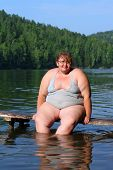 image of flabby  - overweight woman sitting on stage in lake - JPG