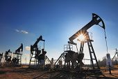 stock photo of polluted  - working oil pumps silhouette against sun - JPG