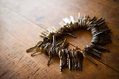 stock photo of locksmith  - Many old keys on a well used old wooden desk - JPG