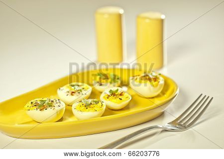 Hard boiled eggs, sliced in halves served on yellow plate