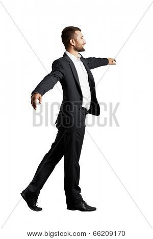 smiley businessman walking on invisible rope over white background