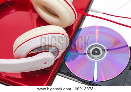 Portable Computer With Dvd Disc And Red White Headphones