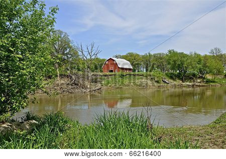 Red barn on eroding river bank