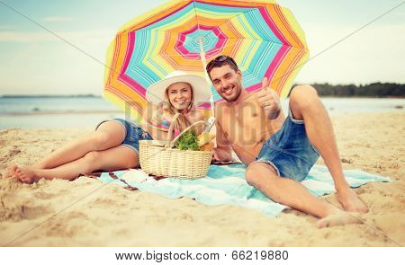 summer, holidays, vacation and happy people concept - smiling couple lying on the beach under colorful umbrella and showing thumbs up