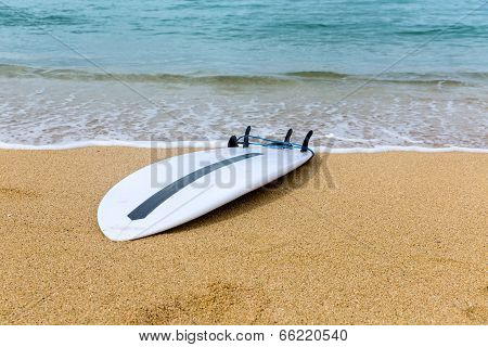 Surfboard Lying On Sand Near The Ocean
