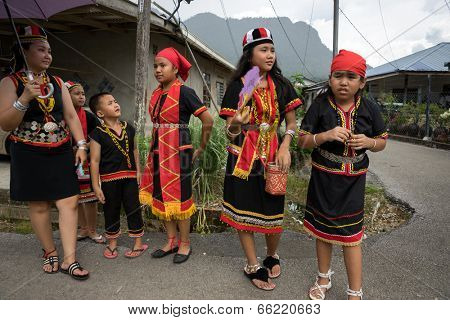 SARAWAK, MALAYSIA: JUNE 1, 2014: People of the Bidayuh tribe, an indigenous native people of Borneo, in traditional costumes, wait for the street parade to pass celebrating the Gawai Dayak festival.