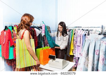 Young Woman In Shop Standing Near Cashiers Desk