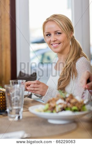 Portrait of beautiful young woman having food at coffeeshop