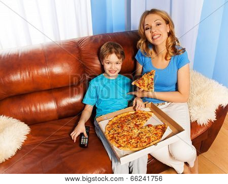 Happy Boy And Mother Eating Pizza On The Couch