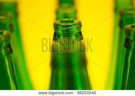 Ten Green Bottles In Three Rows Shot With Yellow Light.