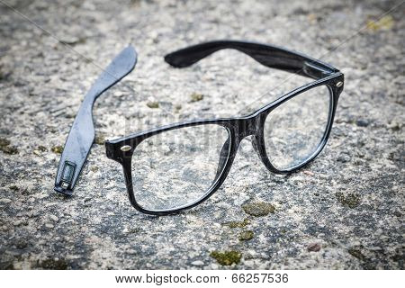 Broken black glasses fallen on tarmac