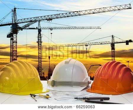 Safety Helmet And Engineering Plan With Drawing Instrument On Engineer Working Table Against Crane C