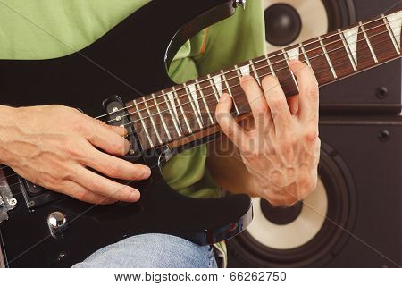 Hands of musician put guitar chords close up