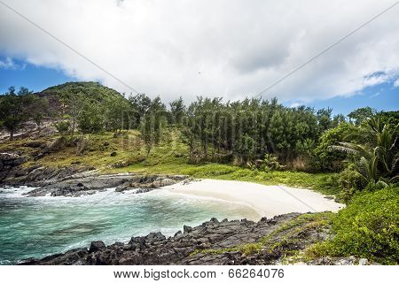 Small Sandy Beach Between Frozen Lava Flows Of Tropical Volcanic Island