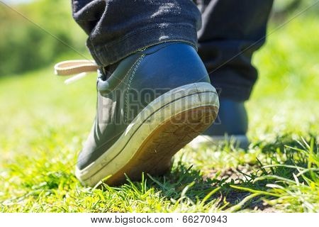 Walking Outdoor. Close Up Image Of Walking Feet In Shoes On Grass