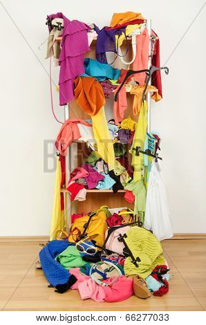 Untidy cluttered woman wardrobe with clothes and accessories falling out of a shelf.