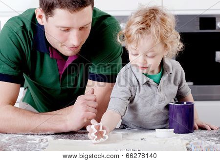 Father And Son Bake Muffins In The Kitchen