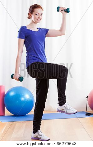 Smiling Woman Exercising Using Dumbbells