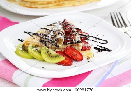 Delicious pancakes with strawberries and chocolate on plate on table