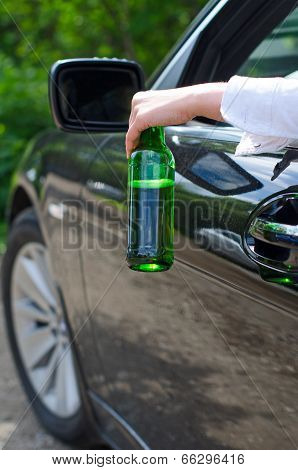 Driving Under The Influence. Female Hand With Bottle Of Beer.