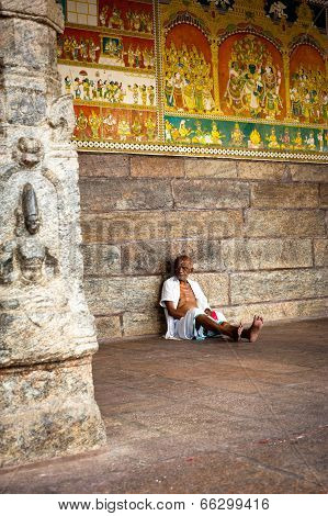 indian man pilgrim resting inside ancient colonnade of Meenakshi Temple