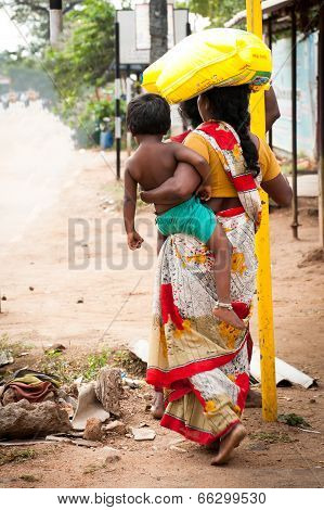 Indian woman in colorful sari with baby carrying bale on head at crowded street of Indian city