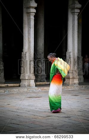 Indian woman in colorful sari carrying bale with offerings for religious ritual at Meenakshi Temple