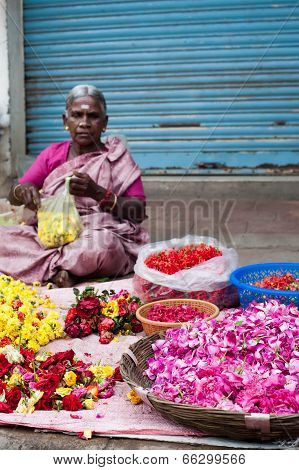 Indian women selling colorful flower garland at street market place