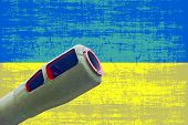 foto of artillery  - Artillery cannon taken closeup against of destroyed Ukrainian flag - JPG