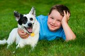foto of cattle dog  - Child lovingly embraces his pet dog outdoors - JPG