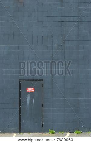 Metal Fire Door Set Into A Blue-Gray Brick Wall