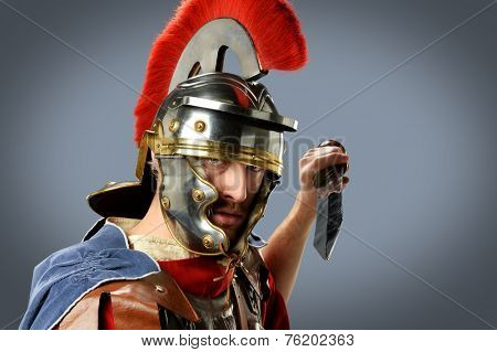 Roman soldier brandishing sword over neutral background