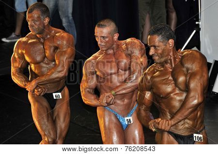 Three Bodybuilding Contestant Showing Their Best In A Line Up