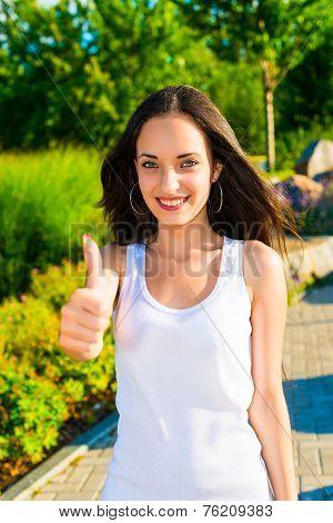 Smiling Young Woman Lifts Thumb