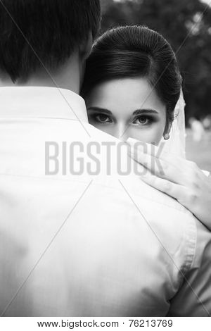 Beautiful Bride In Her Wedding Day Looking In Camera From The Back Of A Groom, Touching Him On A Sho